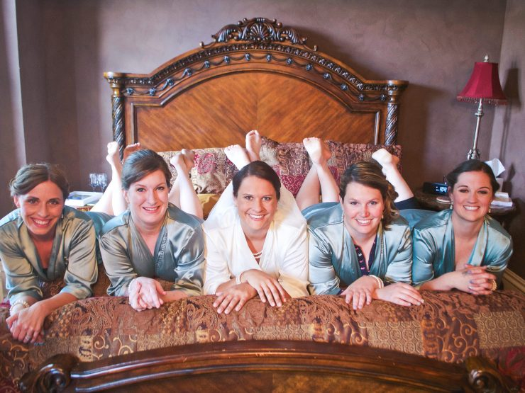 smiling bride and bridesmaids laying on bed
