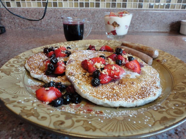 crunch berr pancakes trimmed with strawberries and blueberries
