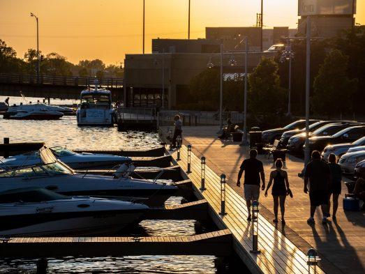 people walking along riverwalk with boats on one side and cars on the other