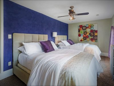 Casa bedroom with two beds with white linens and blue wall