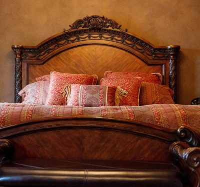 bed in Belle Room with red and brown linens