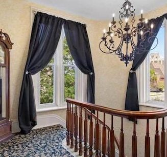 upstairs with grandfather clock, blue curtains, chandelier