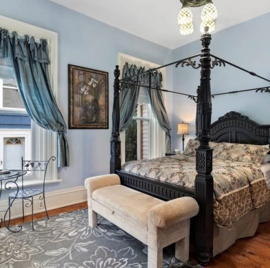 bedroom with blue walls and curtains, ornate 4-poster bed